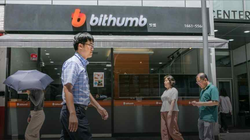 Korean man in checked shirt and glasses walking in front of Bithumb building