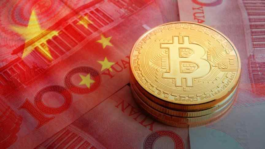 a stack of gold bitcoins laid on Yuan bills