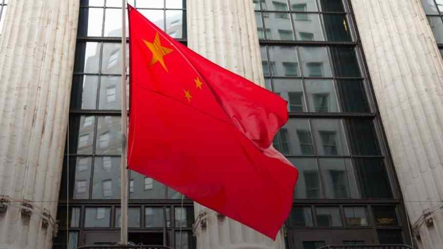 Chinese flag in front of a tall building