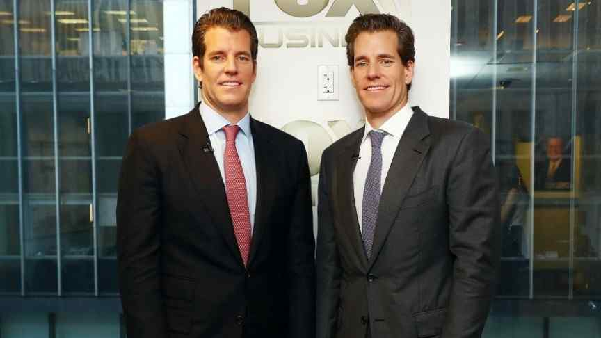 Winklevoss twins in suits, grey and red ties, standing in front of building