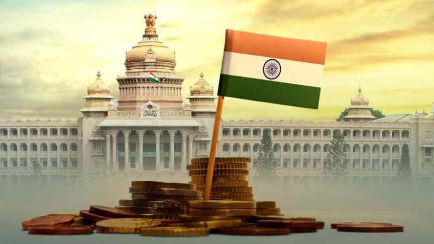 India's flag in the middle of a stack of coins, on background of Indian government building