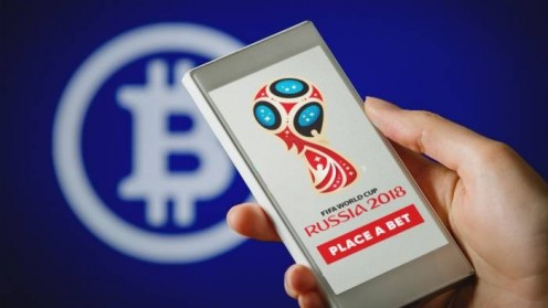 Hand holding smartphone showing FIFA 2018 Russia logo and PLACE A BET button on blue background with Bitcoin logo