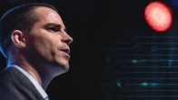 Roger Ver seen from his right profile, wearing a suit looking into distance. Black background and red spotlight pointing at Ver.
