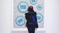 A woman wearing black and blue backpack standing in front of a painting of blue coins saying IAMACOIN on blurry background