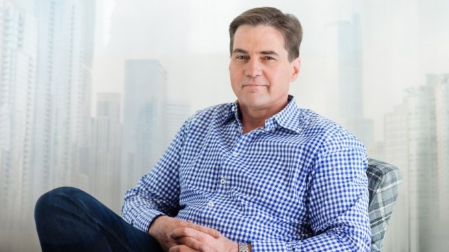 Craig Wright in blue checkered shirt, sitting with hands crossed on lap