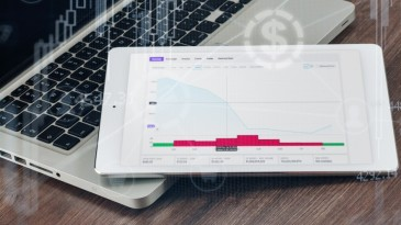tablet showing crypto chart lying on laptop