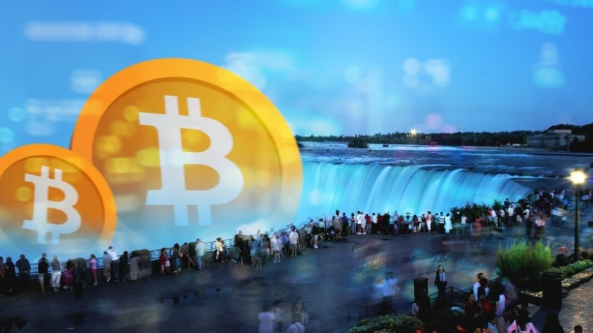 group of people standing around Niagara Falls, big bitcoin logos in orange