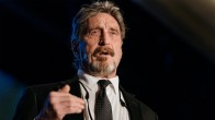McAfee in suit mid speech, dark backgorund