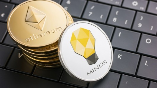 A stack of Ethereum gold coins and one white Minds coin placed on black keyboard